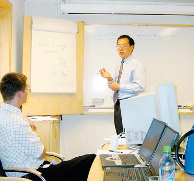 李安(右)与外国专家讨论技术问题.人民视觉